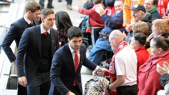 Luis Suarez shakes hands with a fan as Liverpool players arrive at Anfield for the Hillsborough service.