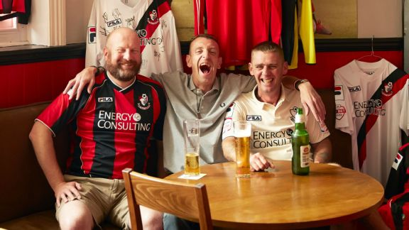 Lance Phayer (centre) with two friends sit at a table in the Queens Park Pub in Bournemouth surrounded by part of his huge collection of Bournemouth football shirts. 2015